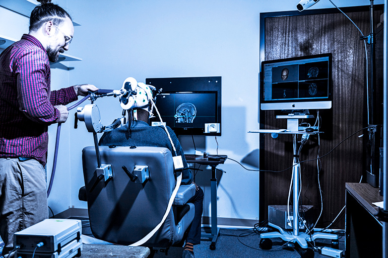 A researcher sets up sets up the coil that will deliver the Senders' responses directly to the brain.