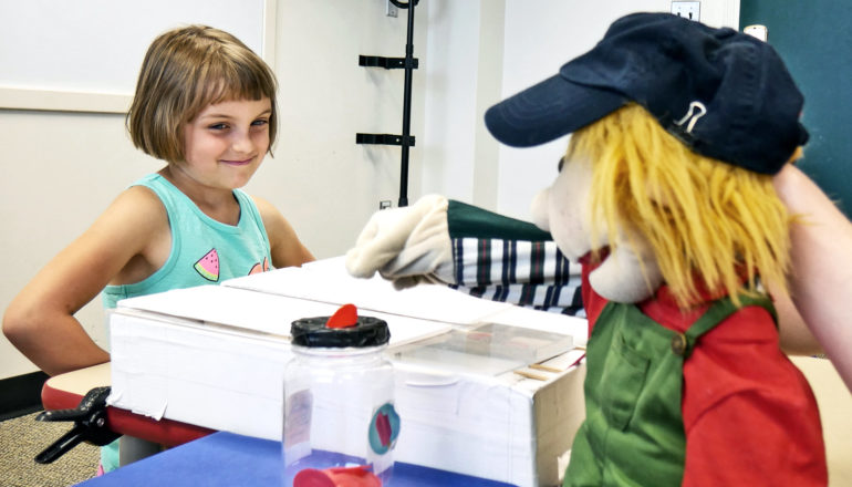 A young girl plays the trust game with a puppet