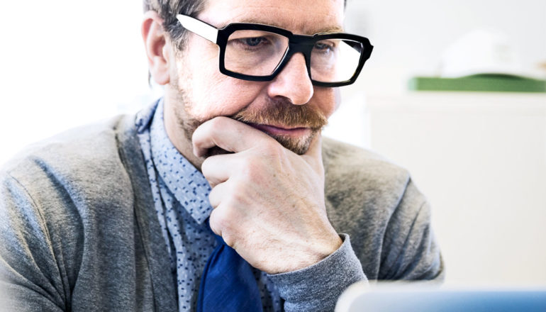 man in thought on computer (hiring bias concept)