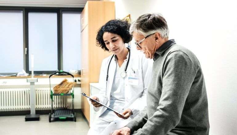 physician and older men look at chart together
