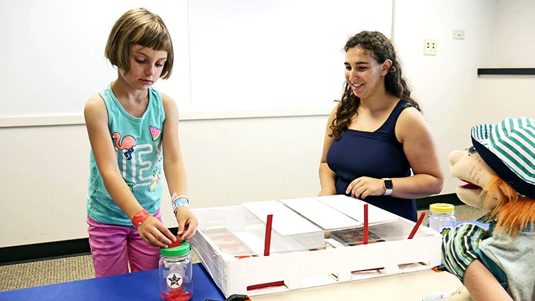 """A girl places coins in her """"bank"""" during the """"trust"""" experiment involving a puppet"""