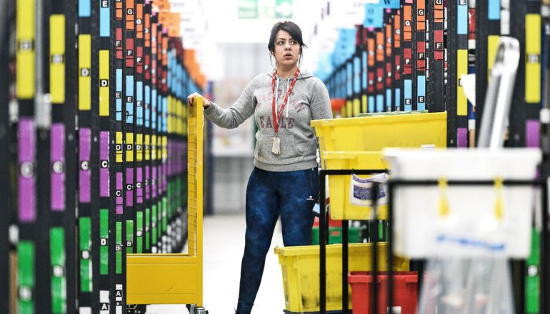 An Amazon warehouse worker looks slightly confused as she stands in between rows of organized and color coded products while holding a rolling bin