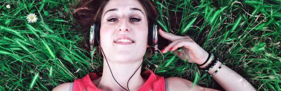 woman lies in grass with one arm raised to hold silver headphones on her head - listening to podcasts
