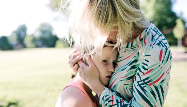 woman consoles preteen girl by holding her close, hands on her head