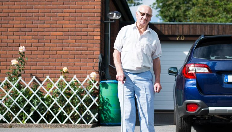 elderly man stands in driveway next to car