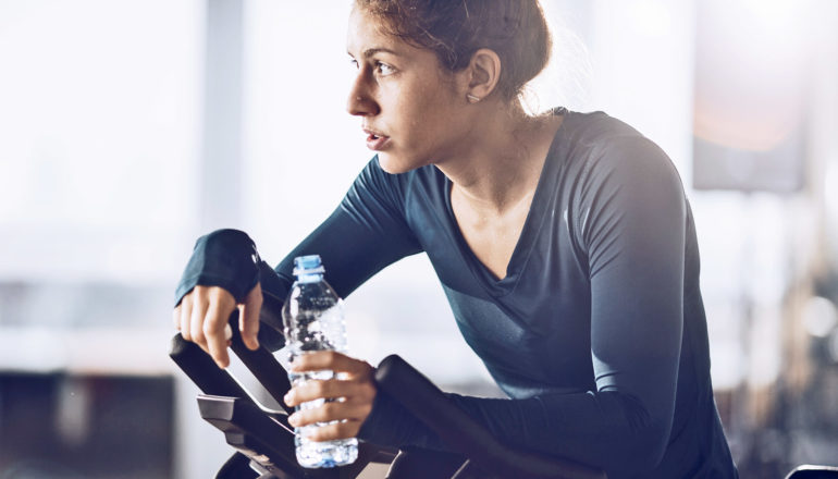 sweaty woman with neutral expression rests on stationary bike holding bottle of water