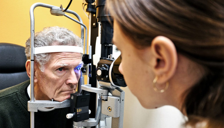 The image shows a man getting an eye exam. (vision impairment concept)
