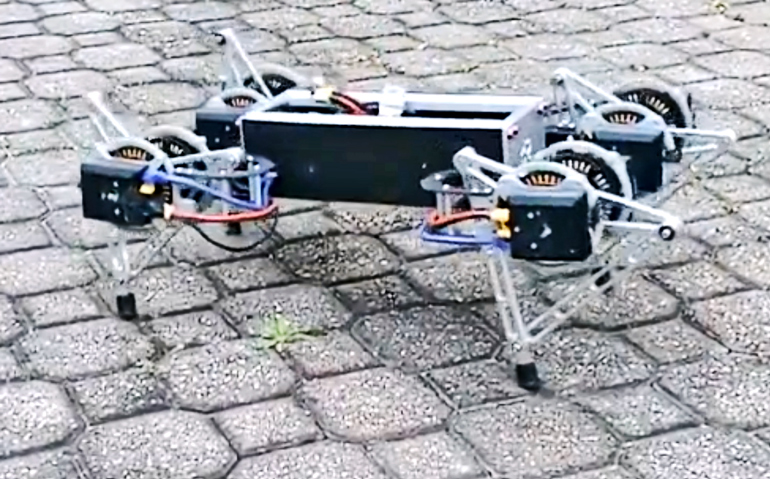 A four-legged robot stands on a outdoor path, with wires coming out of the main body and going into motors on the legs