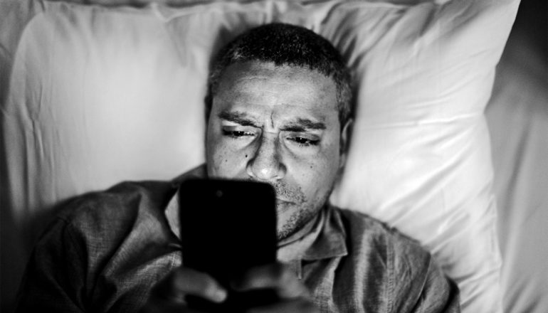 The image shows a man in bed looking at his phone with frustration.