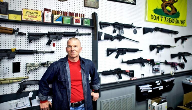 The gun shop manager, wearing a red t-shirt with a blue over-shirt, leans back on a counter in front of a white wall displaying a range of guns