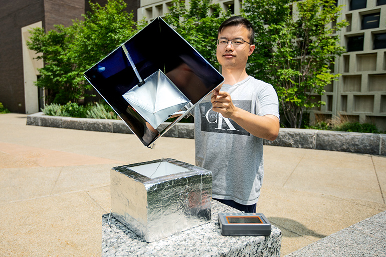 Zhou holds the solar shelter removed from a smaller box to show its insides, a darkly reflective interior in which a reflective panel is suspended