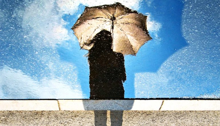 A person holds an umbrella while looking down at their reflection in water, which shows the sky behind them is clear and blue