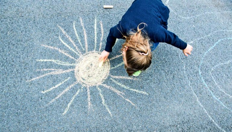 A young kid in a navy shirt uses chalk to draw a yellow sun on some asphalt
