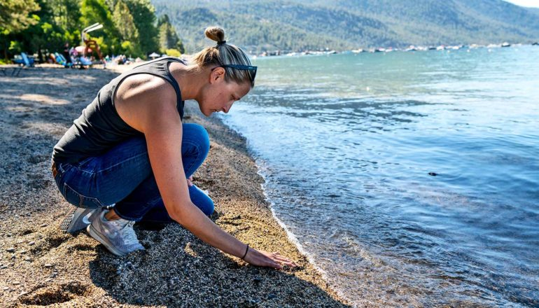 A researcher kneels on the shore of Lake Tahoe. (microplastics concept)