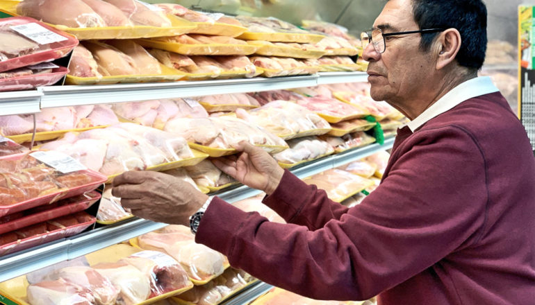 The image shows a man buying chicken at the supermarket. (salmonella concept)