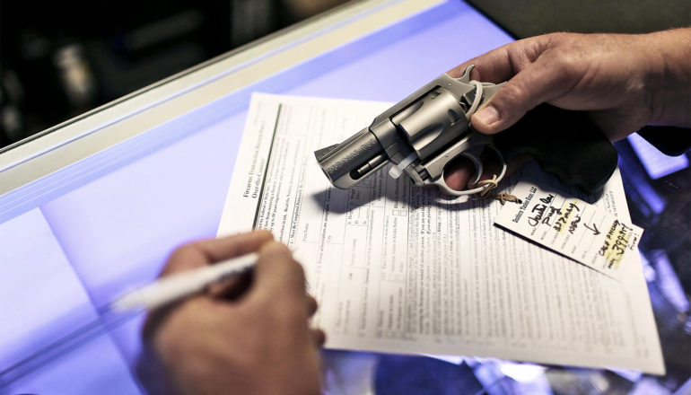 The image shows a man filling out background check paperwork with a gun in hand. (Universal background checks concept)