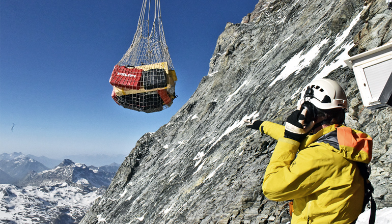 A researcher in a helmet and yellow jacket on the Matterhorn points at a suspended pack of supplies being hoisted up the mountain