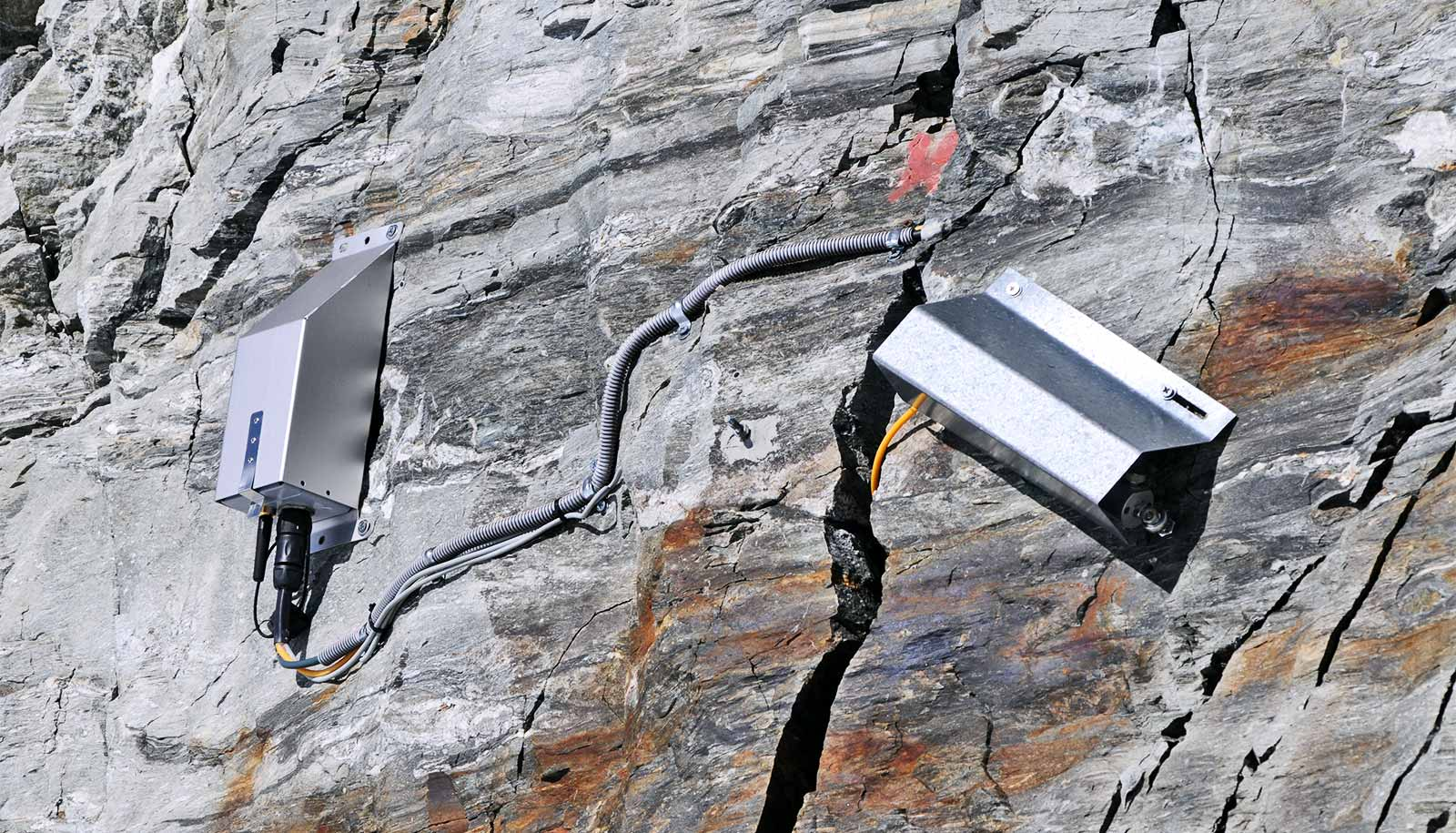 Two metal boxes attached to the rock have wires running into a crack