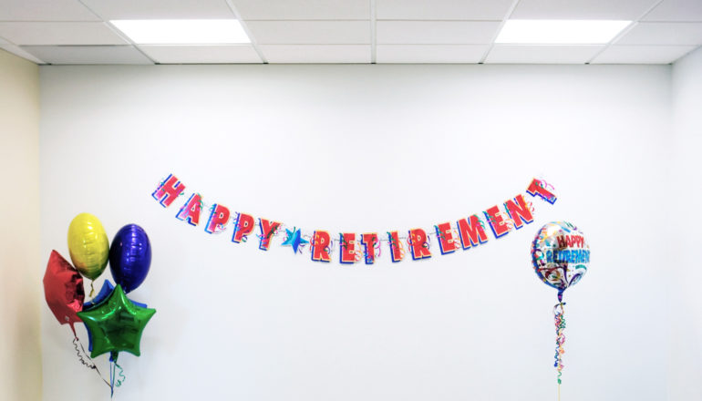 """happy retirement"" banner on wall and balloons in otherwise blank room with panel ceiling and fluorescent lights"