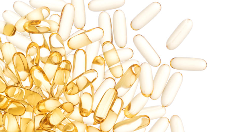 clear golden capsules spill from a pile on the right