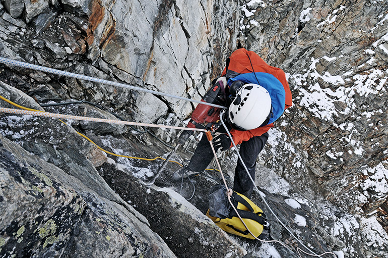 A researcher in climbing gear drills into the rock while hanging from a rope