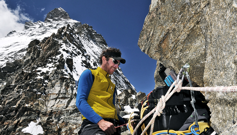 Beutel stands in front of a mountainous peak wearing a blue shirt, yellow vest, sunglasses, and a visor, while working on a box with wires coming out of it attached to the rock.