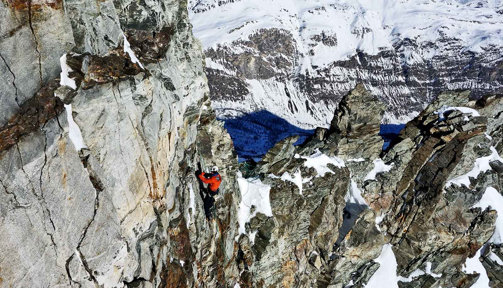 Jan Beutel climbs the massive mountain in a red jacket and safety gear, his body tiny against the scope of the Matterhorn