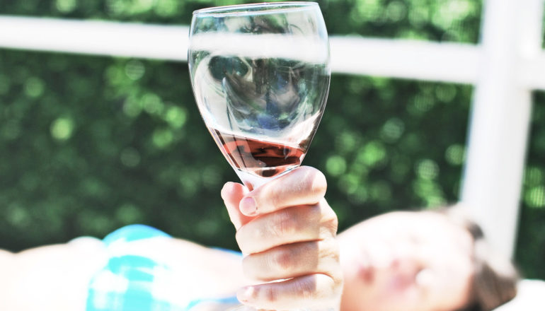 woman holds up her wine glass to the camera while lying down in a swimsuit. (resveratrol concept)