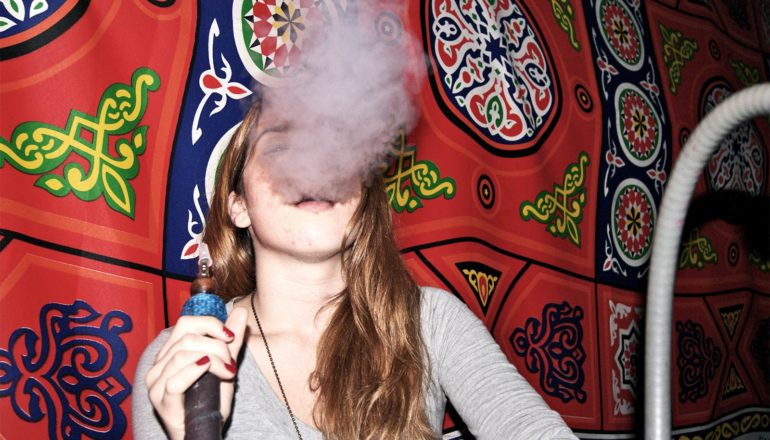 The image shows a young woman smoking hookah with a wall tapestry behind on the wall behind her. (hookah concept)