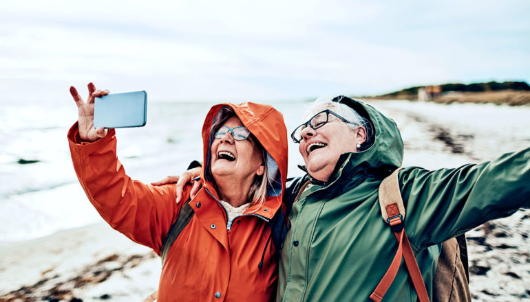 Two friends in rain coats take a selfie on the beach while laughing