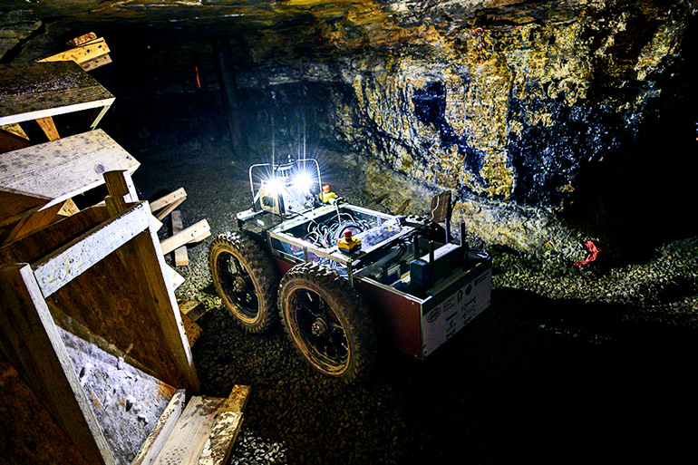 The robot moves through the dark test mine with its headlights on.