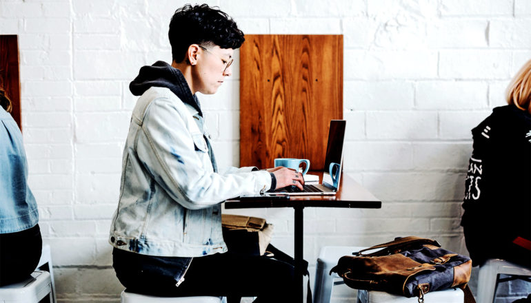 A person wearing a jean jacket and a short haircut in profile uses their laptop at a cafe table against a white wall