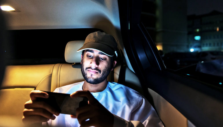 A young man wearing a baseball cap sits in the backseat of a car watching video on his phone at night.