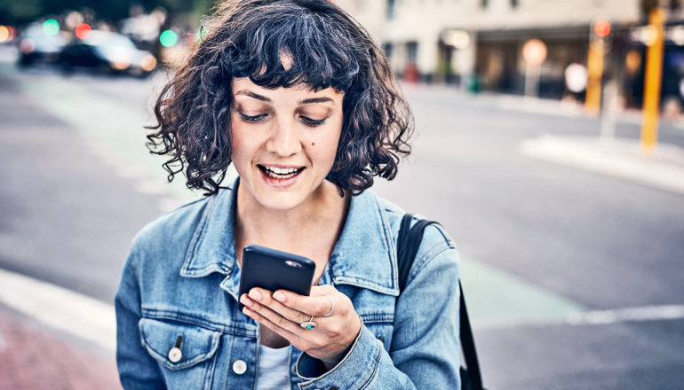 The image shows a young woman using phone on the street. (voting online concept)