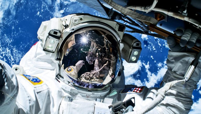 An astronaut takes a selfie during a space walk, with the Earth glowing blue in the background