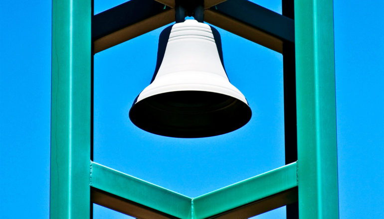 A bell hangs in a green metal structure against a blue sky, with the bell's hole appearing totally black
