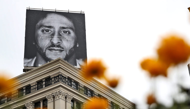 """Billboard atop building says Believe in something. Even if it means sacrificing everything."""" over Colin Kaerpnick's face. Blurry orange flowers in foreground"""