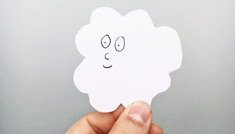 hand holds white paper cloud with friendly face