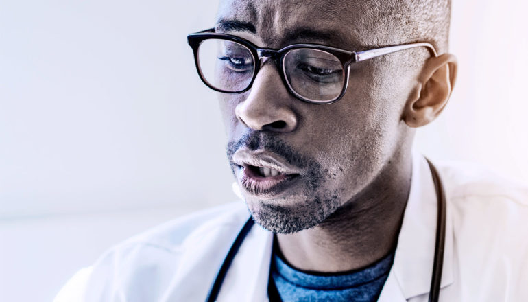 A doctor wearing glasses looks down with focus or concern as he talks to his patient