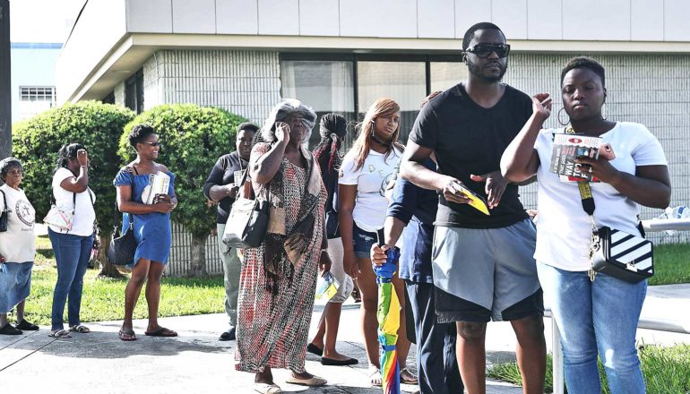 Voters stand outside in a line for early voting