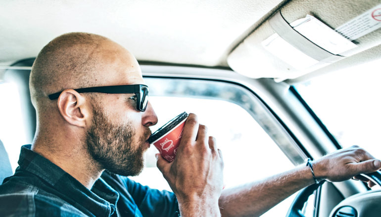 A man wearing sunglasses drives to work while sipping a cup of coffee