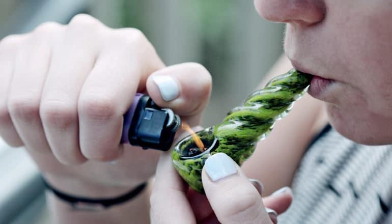 person lights green glass bowl with lighter to smoke marijuana