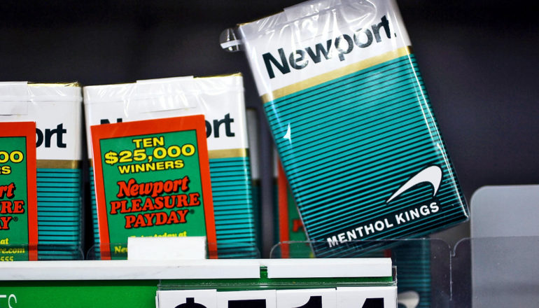 A few packs of menthol cigarettes sit on a shelf at the store, with one pack almost coming off the shelf