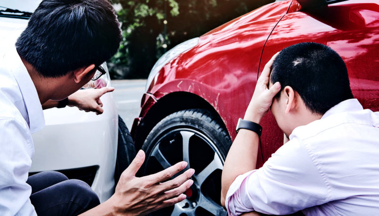 two men kneel by their cars after a crash, with one pointing to the damage and the other holding his head in his hands.