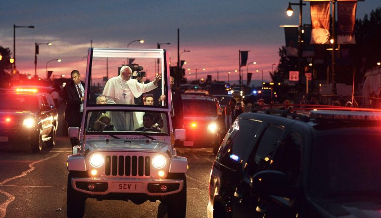 pope francis stands in glass-topped vehicle, waves to unseen crowd