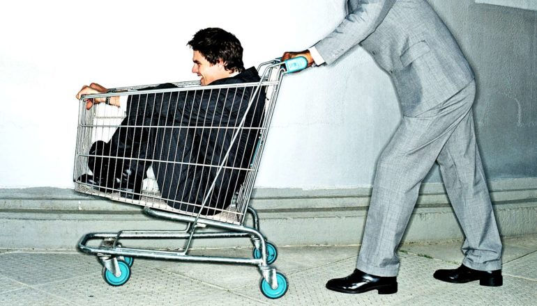 figure in suit pushes person in shopping cart