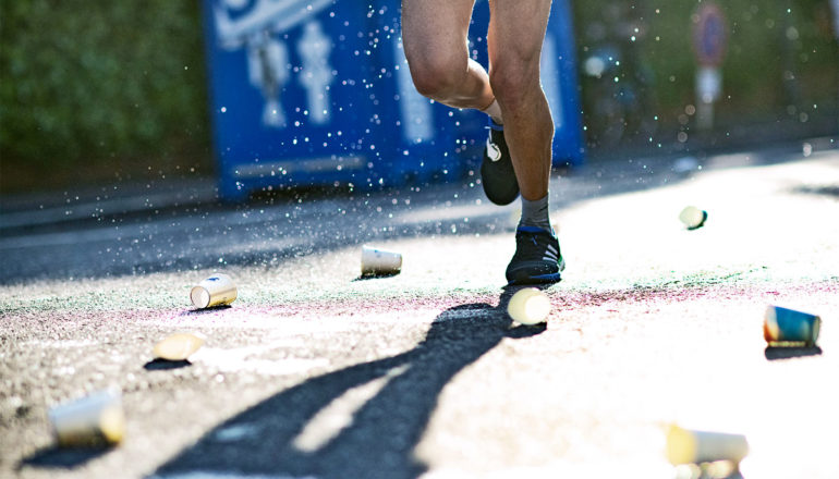 A marathon runner's legs are surrounded by empty paper water cups on the road