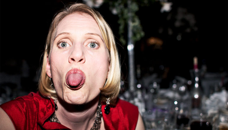 A woman in a red outfit turns to the camera from a table she's sitting at to stick her tongue out