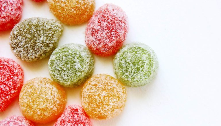 Chewy, colorful candies covered in sugar sit on a white background