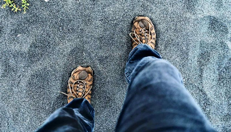 A person in gray jeans with hiking shoes on walks over gray sand
